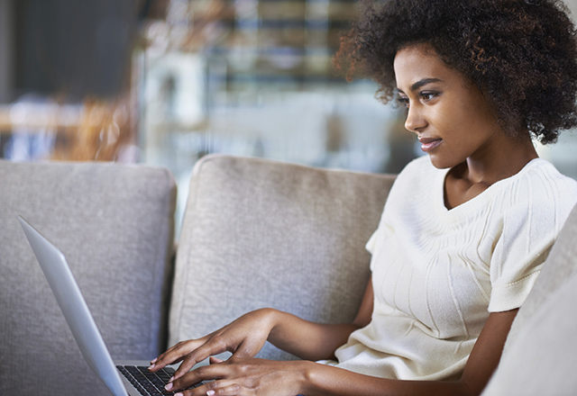 A young woman sits on the couch with a laptop.