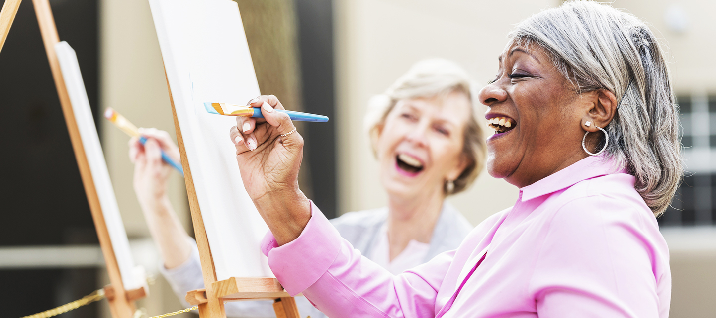 Two multi-ethnic senior women sitting outdoors at easels painting pictures on canvases. The focus is on the African American woman who is holding a paintbrush and looking up at her artwork as she laughs.