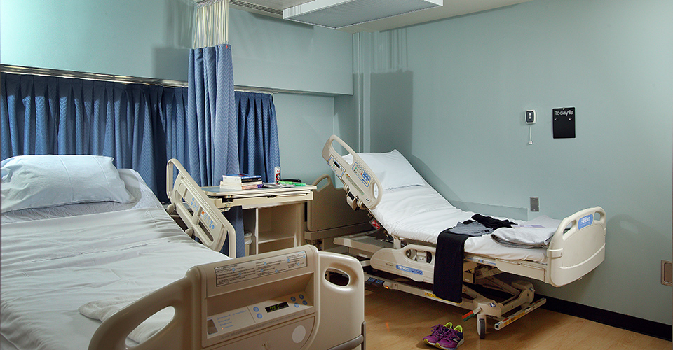 Two hospital beds in a patient room.