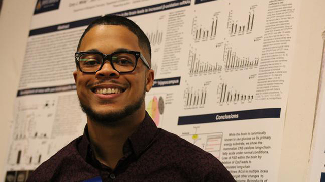Cory White standing in front of research poster.