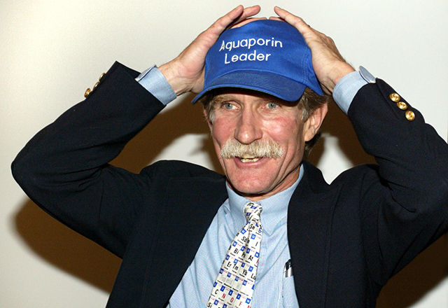 Peter Agre holds his head with both hands in an expression of delighted surprise; he is wearing a hat that reads