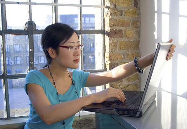 a woman uses her laptop
