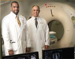 2 doctors wearing white coats stand in front of a CT scanner