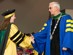 Dean/CEO Edward Miller congratulates a medical school graduate during the 116th convocation ceremony, May 24.