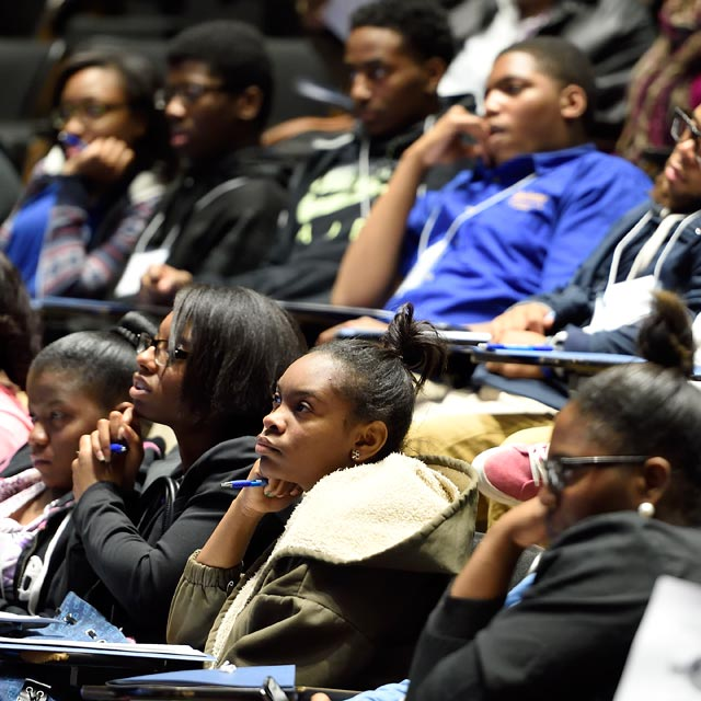 The photo shows students at the Henrietta Lacks Symposium.