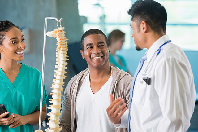 patient nurse doctor looking at spine model