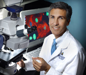 photo of Dr. Nicholas Maragakis sitting in front of a microscope and computer