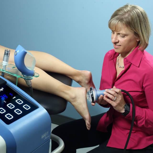 A therapist using a sound wave machine on a patient's foot