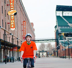 Jacob Landis riding bike through Camden Yard alley.