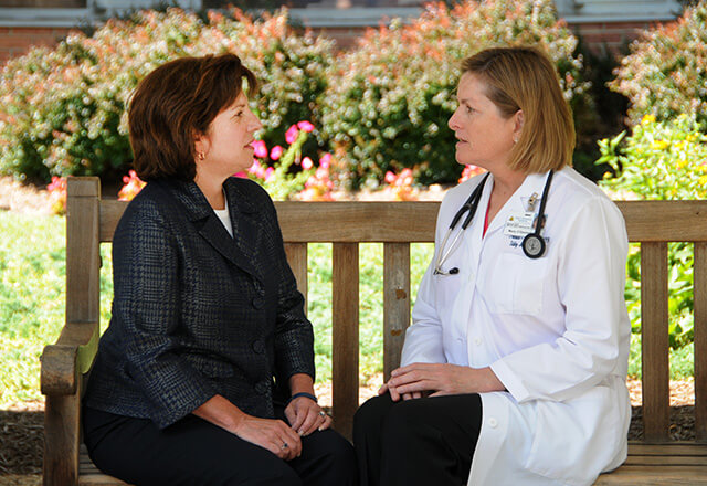 Female doctor talking to a woman on a bench outside