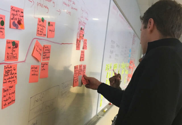 Entrepreneurial Accelerator participant placing post-its on a whiteboard