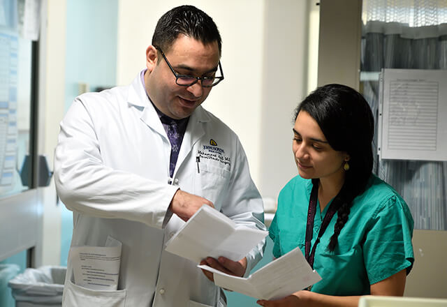 A burn fellow and a nurse review a document together.