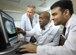 Pancreatic surgeon Dana Andersen, endoscopy chief Patrick Okolo and Pancreatitis Center director Vikesh Singh examine a patient's results.