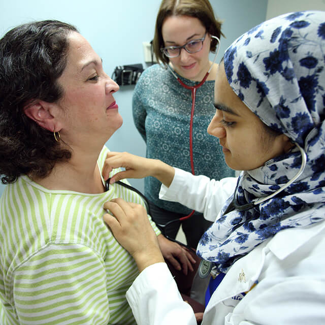 Using a shared stethoscope, med student Anila Chaudhary listens to patient Maria Aponte's heart as internist Fernanda Porto Carreiro looks on.
