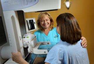 Female doctor directing patient to mammography machine