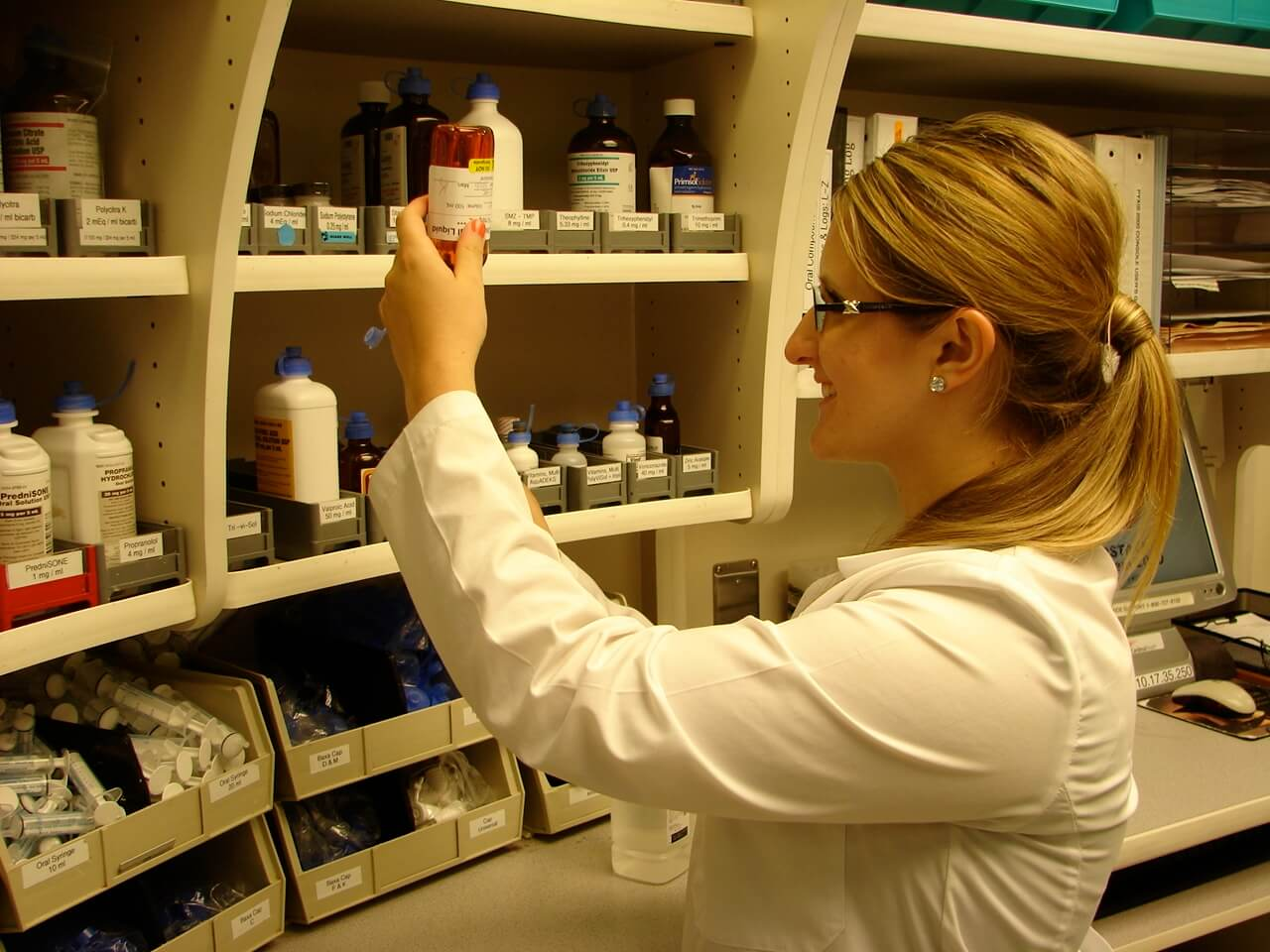 intern looking at a bottle in a pharmacy