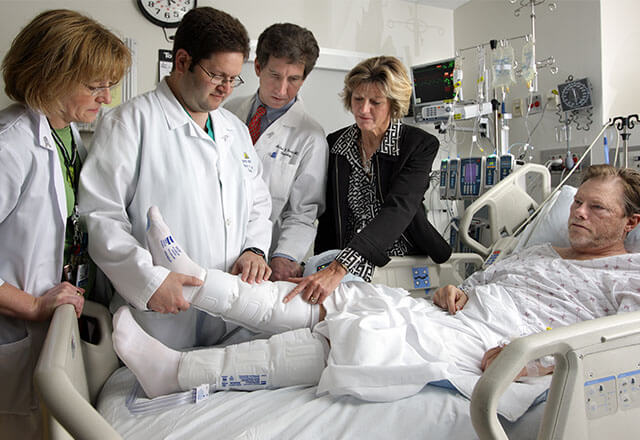 A doctor and a nurse speaking with a patient in a hospital bed
