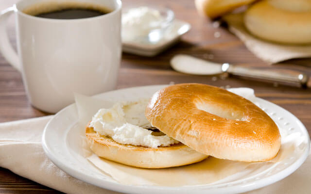 A bagel with cream cheese and coffee
