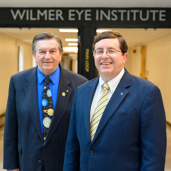 Lions John Shwed, left, and Larry Burton standing inside the Wilmer Eye Institute