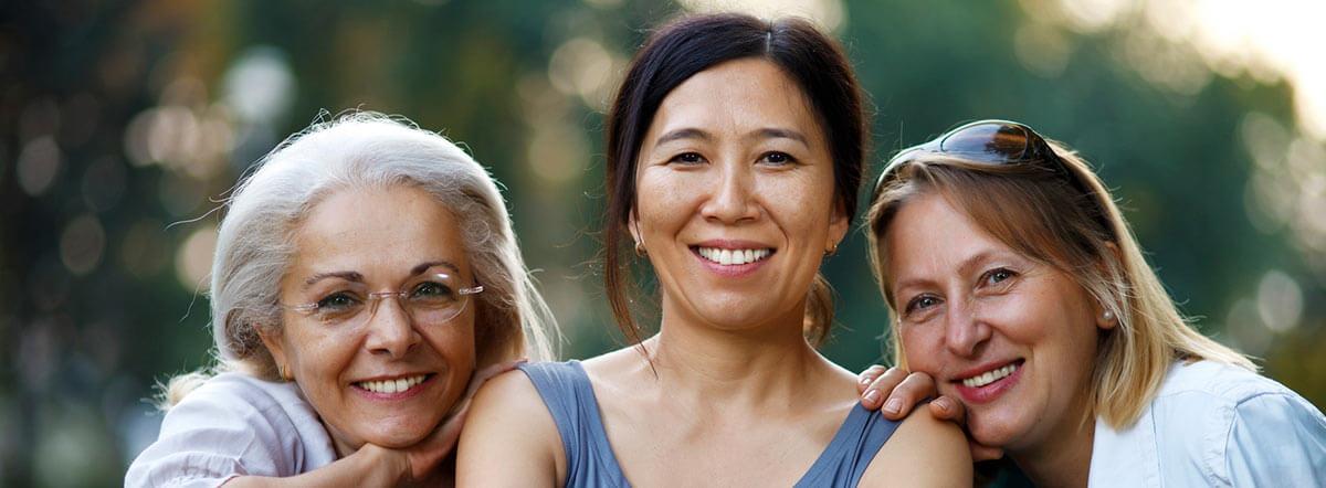 Three women sitting outdoors.