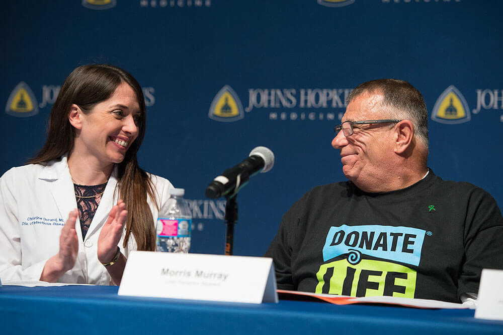 Dr. Durand and patient speaking during a media briefing