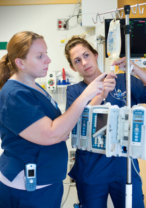 Katie Reeves (left) mentors new nurse Cara McComas in the progressive cardiac care unit. McComas also takes part in the SPRING nurse residency program, which has helped boost retention of new nurse graduates.