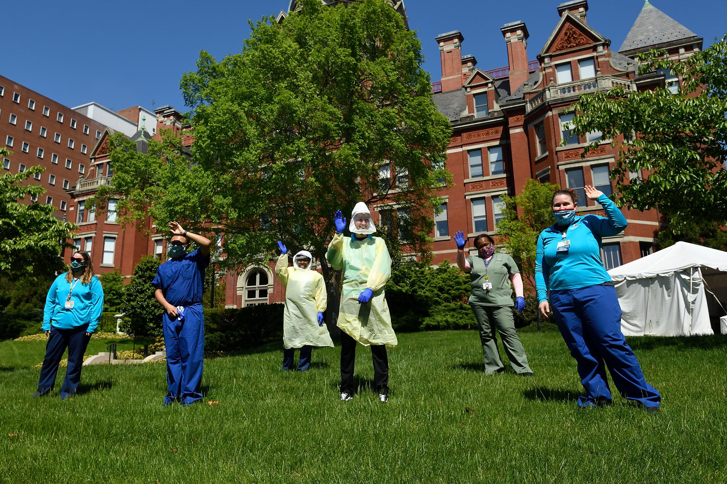 Johns Hopkins employees stand outside of The Johns Hopkins Hospital waving