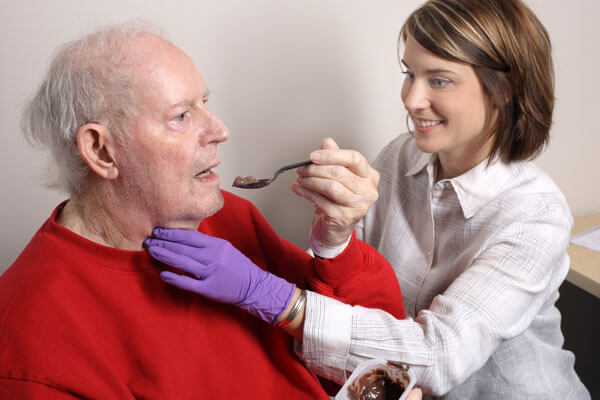 Older male patient feeding himself with help from a female medical staff member