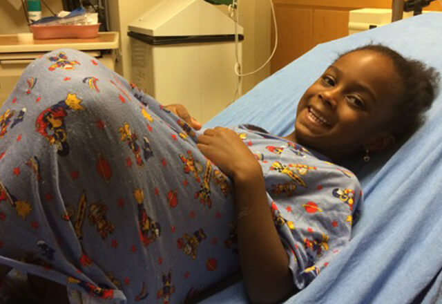 olivia smiles while she lays in her hospital bed
