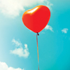 Heart-shaped balloon in a clear sky on a sunny day