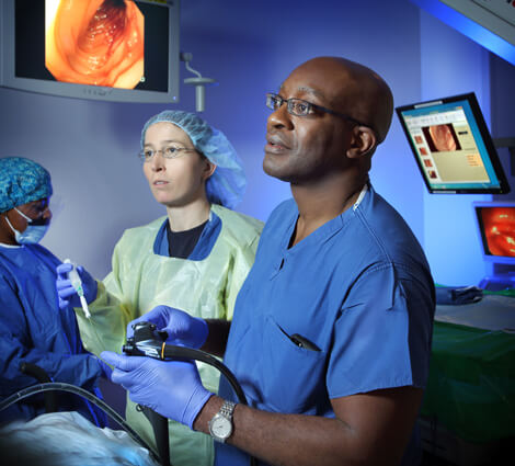 Patrick Okolo, right, assistant Nicole Carr, far left, and nurse Tina McDonald are able to see deep into the middle gut with the latest scoping techniques and technology.