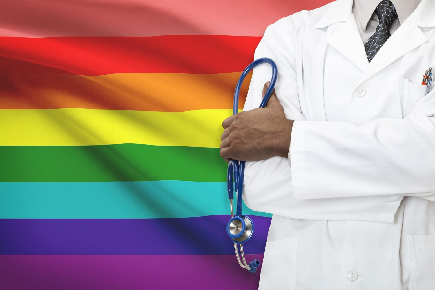 A doctor standing in front of an LGBT flag