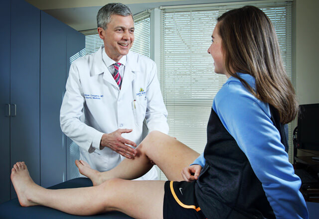 Dr. Andrew Cosgarea, sports medicine expert and orthopedic surgeon, examins a female athletes knee injury