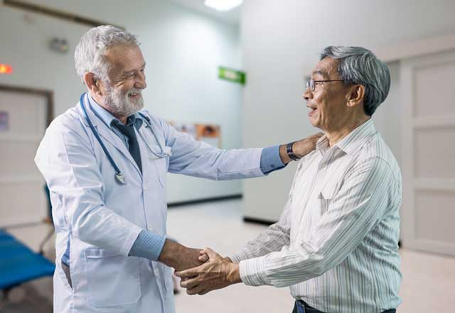 Grey hair doctor shaking hands with patient.