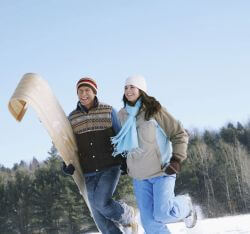 man and woman carrying sled in snow