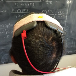 the back of a man's head with two flat objects on top with wires coming out
