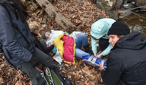 Medical students treat a mock injury in the woods.