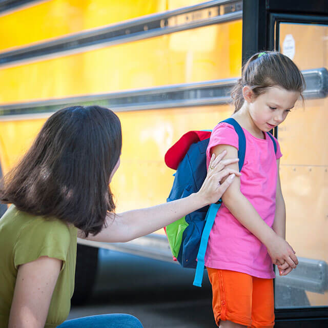 Mom comforts her anxious daughter at the bus stop.
