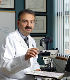 photo of Dr. Ahmet Hoke seated in front of a microscope, holding a slide