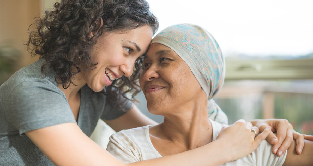 Ethnic adult female cancer patient hugging her daughter