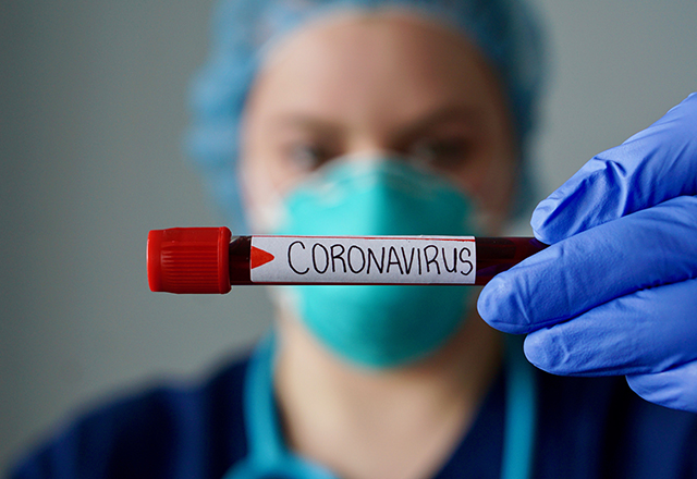 "A healthcare worker wearing a mask holds up a test tube labeled, ""Coronavirus."""