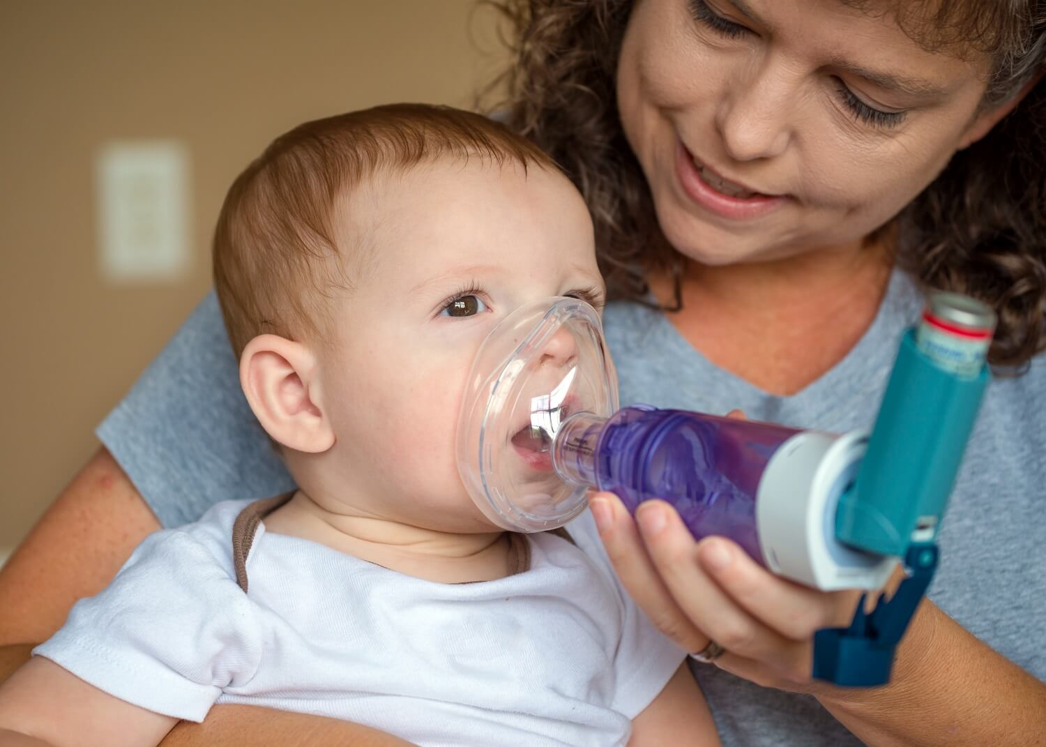 Baby breathing into a inhaler with a spacer