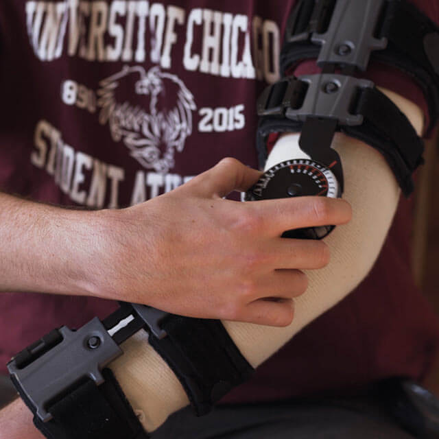 a person wearing a hinged elbow brace after a UCL reconstruction surgery