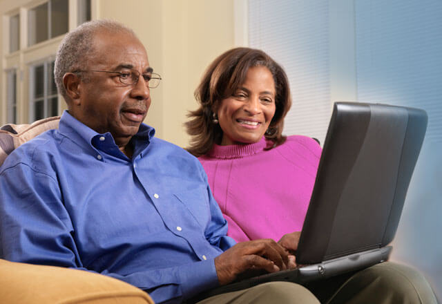 Couple sitting on a couch using a computer together