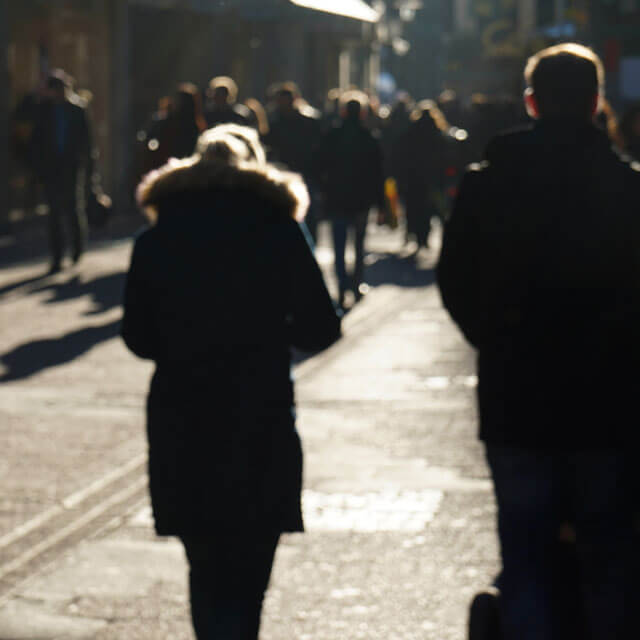 Pedestrians walking along a busy street during the winter.