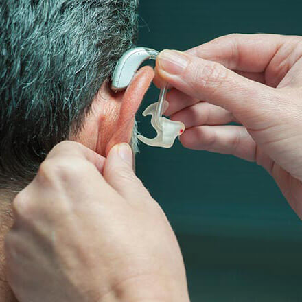 Doctor fits patient for a hearing aid.