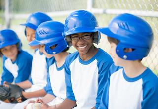 Little league players sitting in the dugout