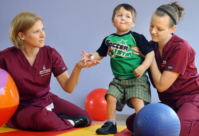 Nurses help a child with physical and occupational therapy