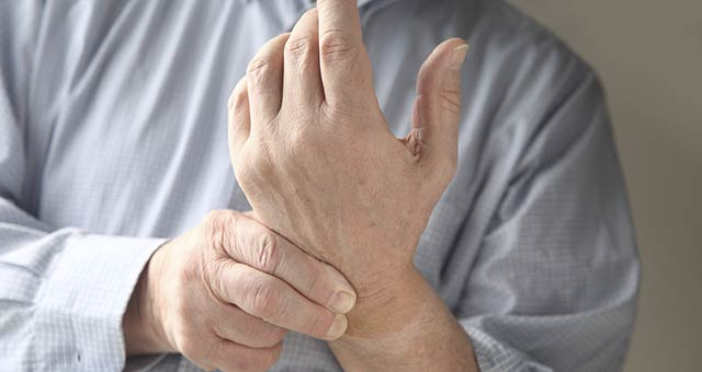 man clutching wrist and hand
