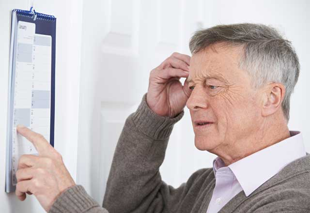 Man looking at his calendar and touching his head